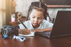 Cute asian child girl using laptop and writing on her notebook royalty free stock photos