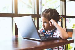 Cute asian child girl using and playing on laptop in the cafe. With fun and happiness royalty free stock image