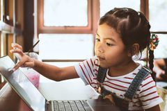 Cute asian child girl using and playing on laptop in the cafe. With fun and happiness stock images