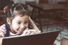 Cute asian child girl using and playing on laptop in the cafe. With fun and happiness royalty free stock images