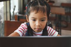 Cute asian child girl using and playing on laptop in the cafe. With fun and happiness stock image