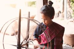 Cute asian child girl using traditional wooden spinning wheel. Cute asian child girl in Thai traditional dress using traditional wooden spinning wheel with fun Stock Photography