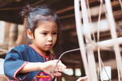 Cute asian child girl using traditional wooden spinning wheel. Cute asian child girl in Thai traditional dress using traditional wooden spinning wheel with fun Royalty Free Stock Images