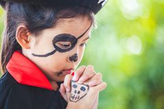 Asian child girl wearing halloween costumes and makeup making hands folded in prayer on Halloween celebration