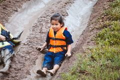 Cute asian child girl having fun to play slider muddy. Cute asian child girl wearing life jacket having fun to play slider with muddy that make from nature in stock photos