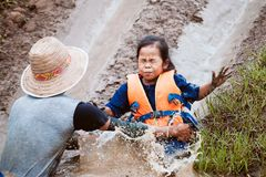 Cute asian child girl having fun to play slider muddy. Cute asian child girl wearing life jacket having fun to play slider with muddy that make from nature in stock photography