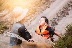Cute asian child girl having fun to play slider muddy. Cute asian child girl wearing life jacket having fun to play slider with muddy that make from nature in stock photo