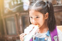 Cute asian child girls with backpack eating pancake after school royalty free stock photography