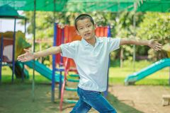 Cute asian child having fun at adventure park. Handsome boy smiling happily at children playground. Asian Caucasian mixed race toddler happily playing in a royalty free stock image