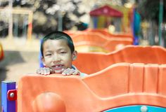 Cute asian child having fun at adventure park. Handsome boy smiling happily at children playground. Asian Caucasian mixed race toddler happily playing in a royalty free stock photo