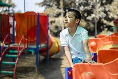 Cute asian child having fun at adventure park. Handsome boy smiling happily at children playground. Asian Caucasian mixed race toddler happily playing in a royalty free stock photography