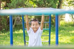 Cute asian child having fun at adventure park. Handsome boy smiling happily at children playground. Asian Caucasian mixed race toddler happily playing in a stock photography