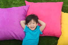 Cute asian child lying with colorful pilows Royalty Free Stock Image