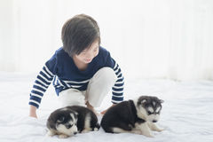 Cute asian child playing with siberian husky puppy Royalty Free Stock Photo