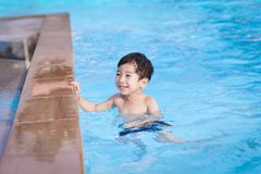 Cute Asian child playing in swimming pool Stock Photo