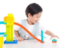 Cute Asian child playing toy cars. On white background isolated Stock Photo