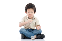 Cute Asian child saving money in glass bottle Stock Images