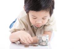 Cute Asian child saving money in glass bottle Stock Photo