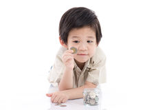Cute Asian child saving money in glass bottle Stock Photography