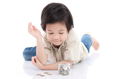 Cute Asian child saving money in glass bottle Royalty Free Stock Image