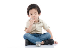 Cute Asian child saving money in glass bottle Royalty Free Stock Photo