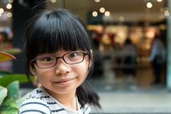 Cute Asian Chinese girl with glasses in park. Cute little Asian Chinese girl with glasses in park smiling Royalty Free Stock Photo