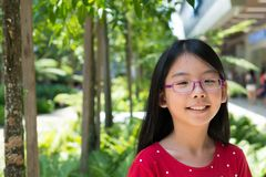 Cute Asian Chinese girl with glasses in park. Cute little Asian Chinese girl with glasses in park smiling Royalty Free Stock Image