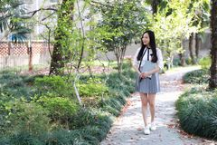 Cute Asian Chinese pretty girl wear student suit in school hold a book walking Royalty Free Stock Photo