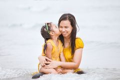 Cute asian daughter kiss her mother with love on beach. In summer vacation Royalty Free Stock Photography