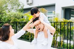 Cute Asian father piggbacking his son along with his wife in the park. Excited family spending time together with happiness. stock photo