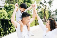Cute Asian father piggybacking his son along with his wife in the park. Excited family raising hands together with happiness. royalty free stock image