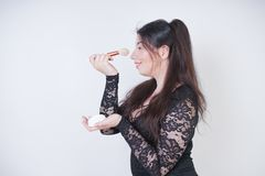 Cute Asian girl in black lace evening dress with powder and a brush in hands on white background royalty free stock photos