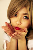 Cute Asian girl. Blowing kisses stock photo