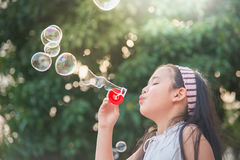 Cute asian girl is blowing a soap bubble Stock Photo