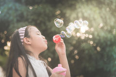 Cute asian girl is blowing a soap bubble Royalty Free Stock Photo
