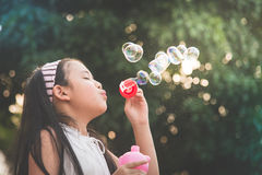 Cute asian girl is blowing a soap bubble Royalty Free Stock Images