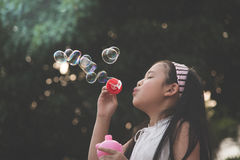 Cute asian girl is blowing a soap bubble Stock Images