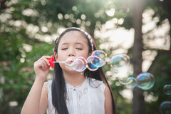 Cute asian girl is blowing a soap bubble Stock Photos