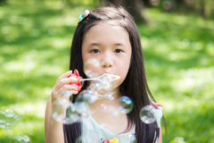 Cute asian girl is blowing a soap bubbles Stock Photo