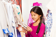 Cute Asian girl with braid choosing clothes Royalty Free Stock Photo