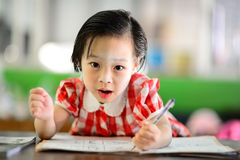 Cute Asian girl doing her homework. Stock Images