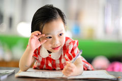 Cute Asian girl doing her homework. Royalty Free Stock Image