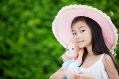 Cute Asian girl. With doll Royalty Free Stock Photos