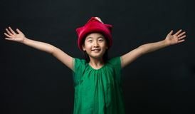 Cute Asian girl dressed in a green dress with a fairy hat and two arms wide open on a black background Stock Photos