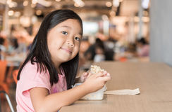 Cute asian girl eating box lunch in food court. Fastfood concept Royalty Free Stock Image