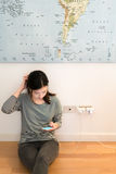 Cute asian girl frustrating with phone's battery, charging on the wall Royalty Free Stock Images