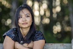 Cute asian girl on a fence on blurred woods background Stock Photos