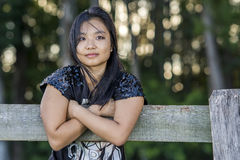 Cute asian girl on a fence on blurred woods background Royalty Free Stock Photos