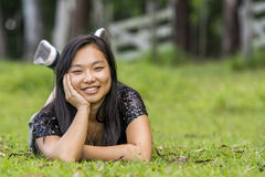 Cute smiling asian girl lying on the grass on blurred woods background Royalty Free Stock Photography