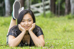 Cute asian girl smiling lying on the grass on the grass on blurred woods background Stock Image